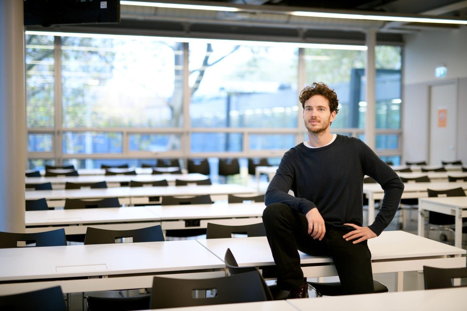 Mannelijke student aan het poseren in een collegezaal van de TU/e
