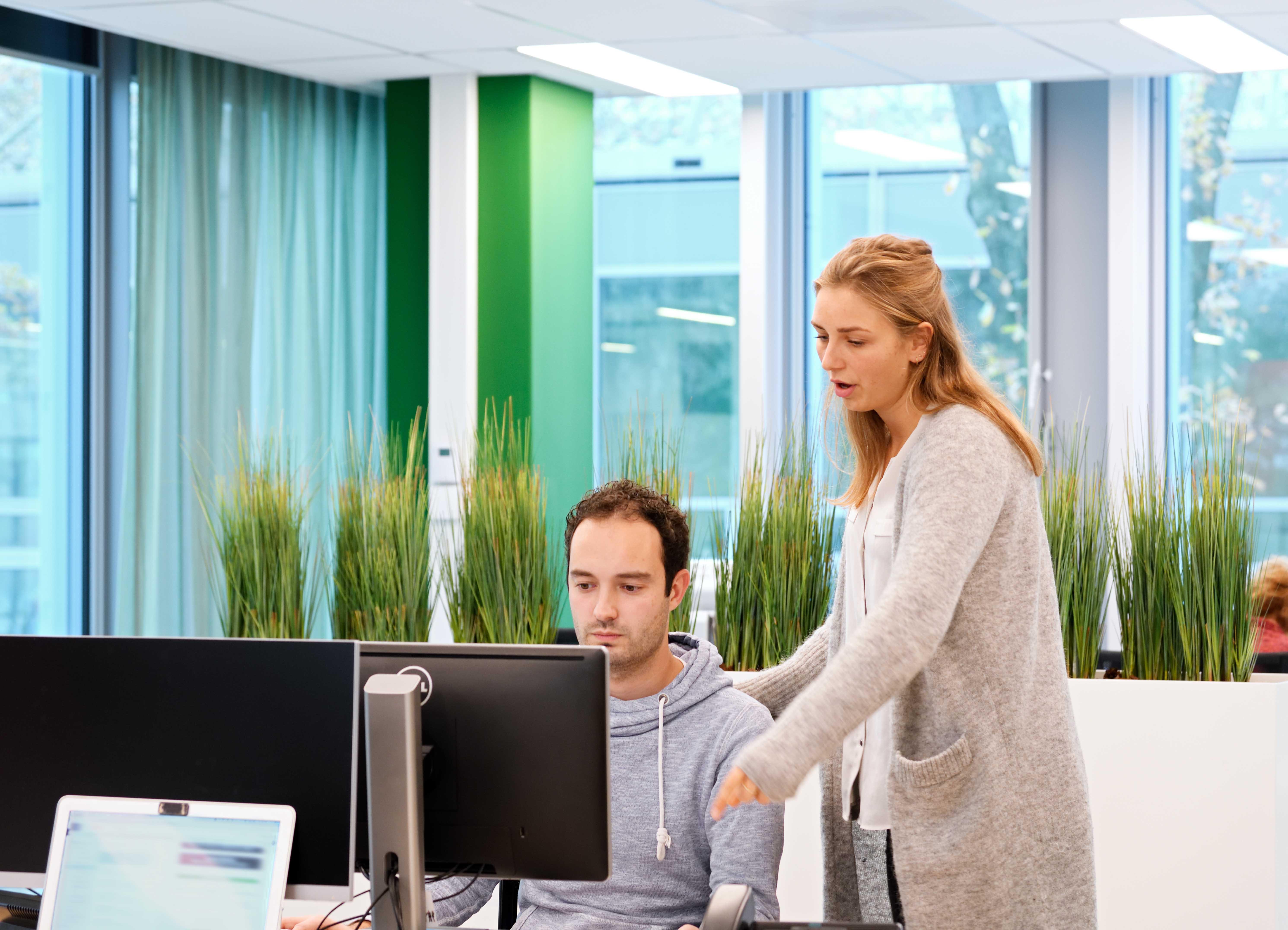 Jongen en meisje op kantoor van EuFlex, Meisje legt jongen iets uit.